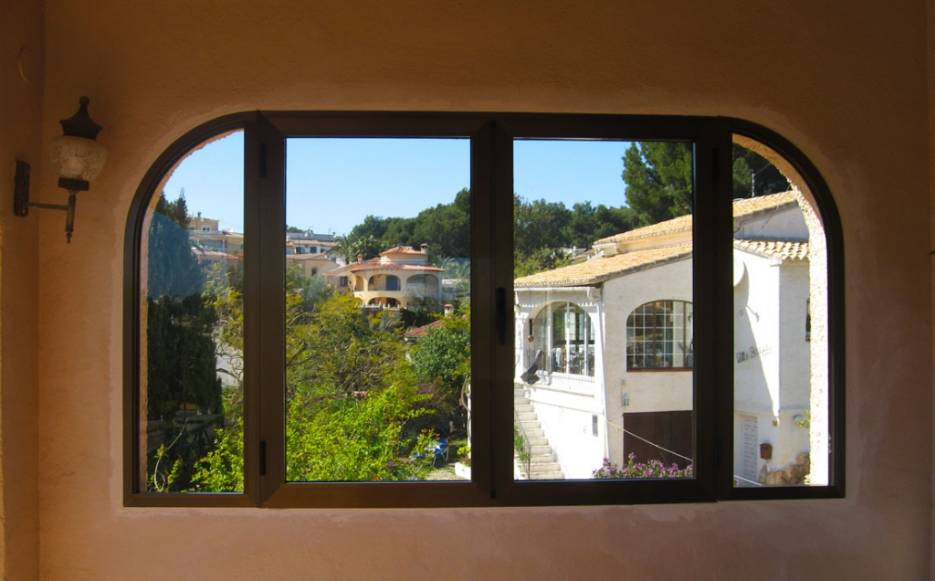 Double opening windows with arched side panels closed